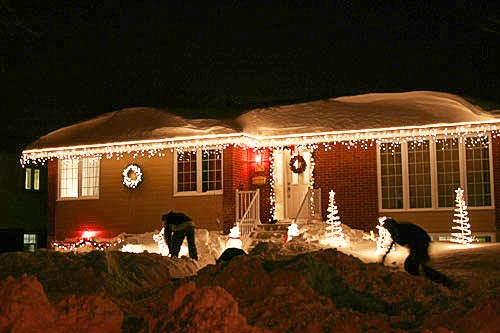 shovelling snow in front of a house decorated with christmas lights