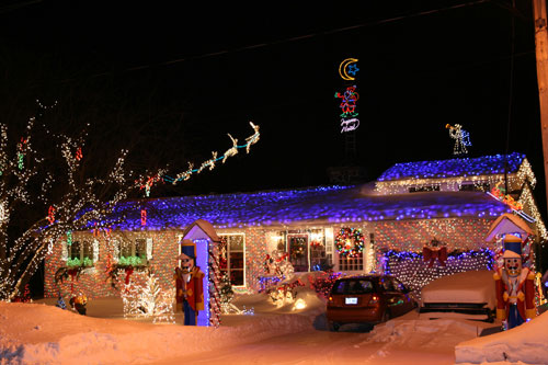 a home decorated in christmas lights after a fresh dusting of snow