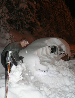 shovelling off car in the dark during early morning