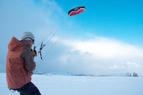 snowkiter in foreground and kite up in sky